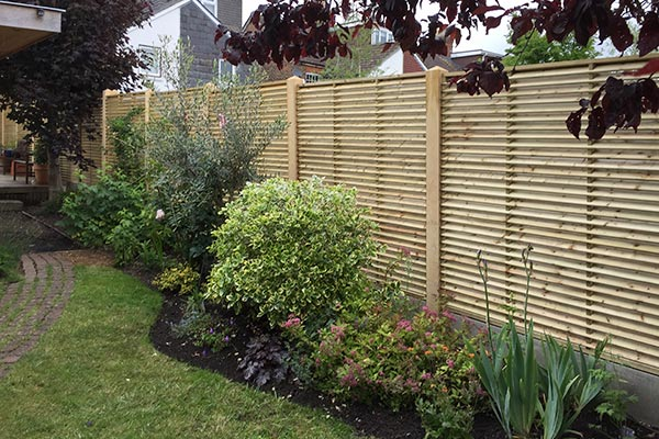 Stunning Louvre fence panel mounted on Green Oak fence posts and smooth concrete gravel boards.